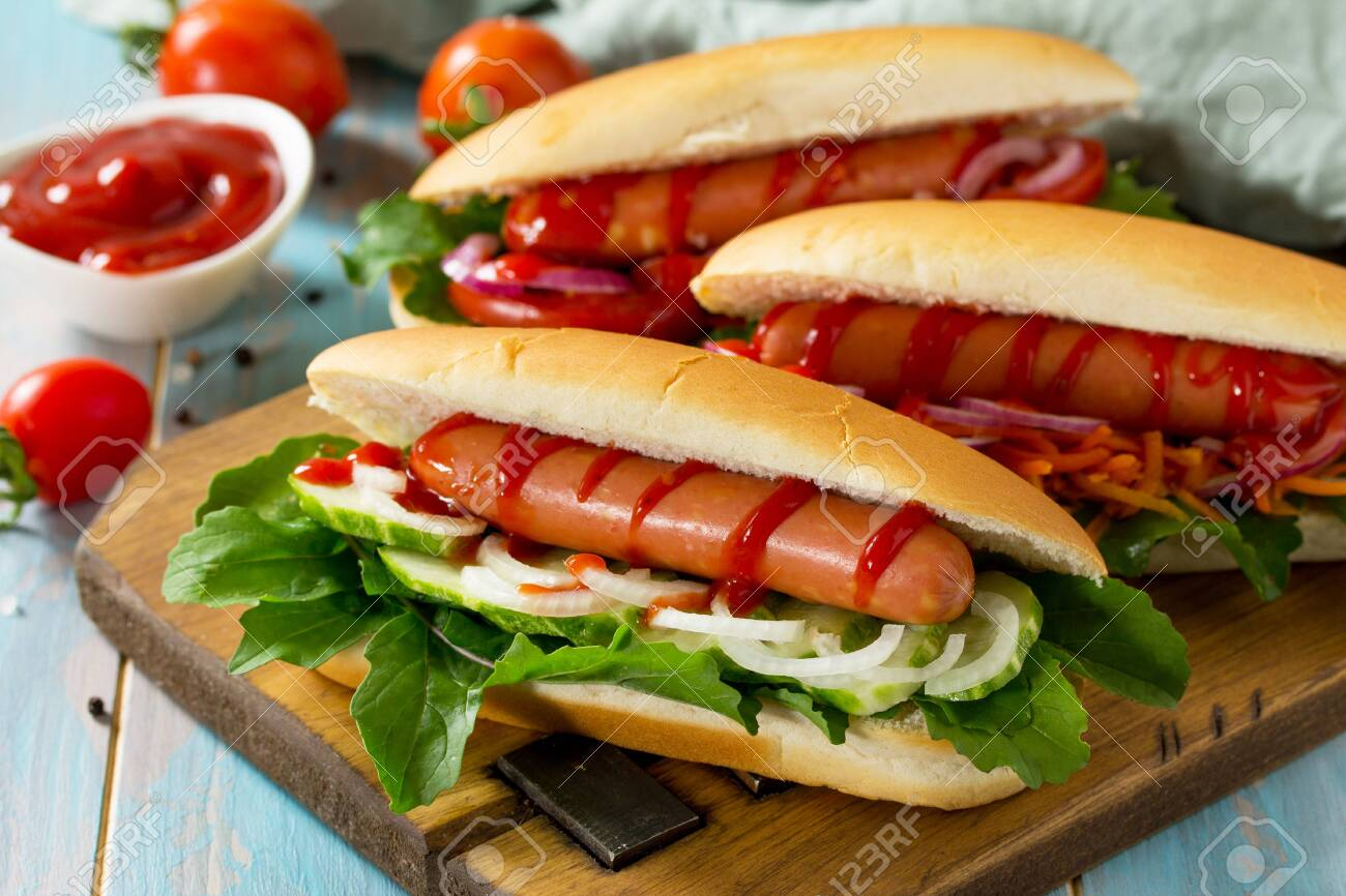 Traditional american fast food. Barbecue grilled Hot dog with fresh vegetables on wooden table. - 128810423