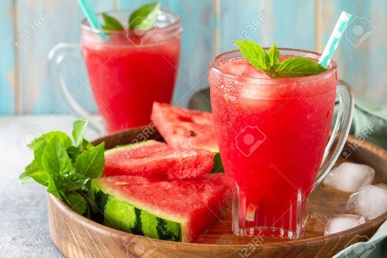 Summer cold drink. Refreshing Watermelon drink in glasses and slices of watermelon on a stone tabletop. - 169810808