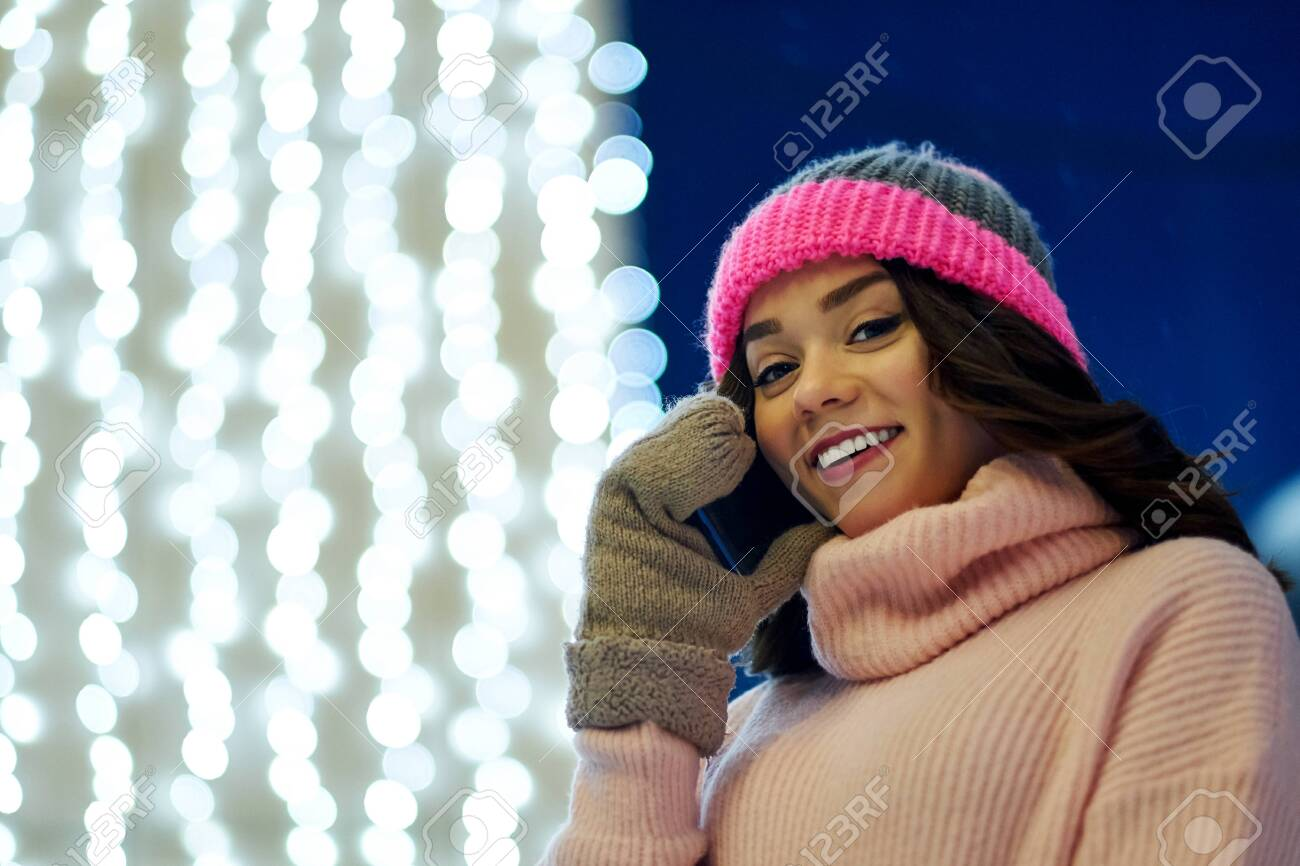 Woman calling congratulate with Christmas or New Year. Female with smartphone at Festive fair. - 133478855