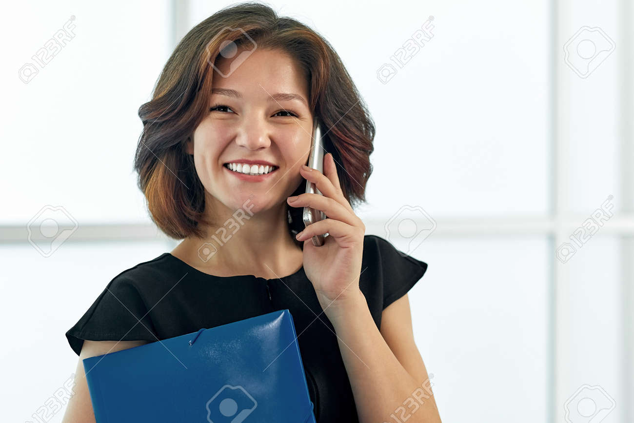 Business woman talking on the phone. Portrait of beautiful girl in office on white background. - 155348803