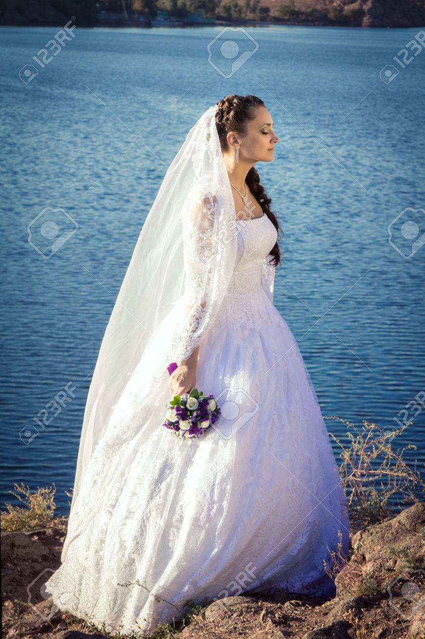 Beautiful Young Bride In A White Wedding Dress, And Long Lacy ...