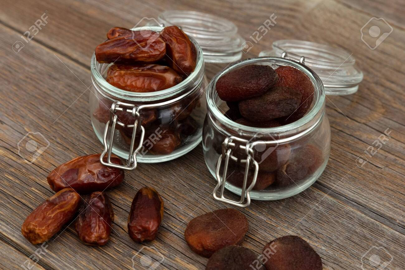 Organic bio dried dates and dried apricots, apricot in glass jars stand on an old rustic wooden table. Dried fruits. Healthy snack - 143821147