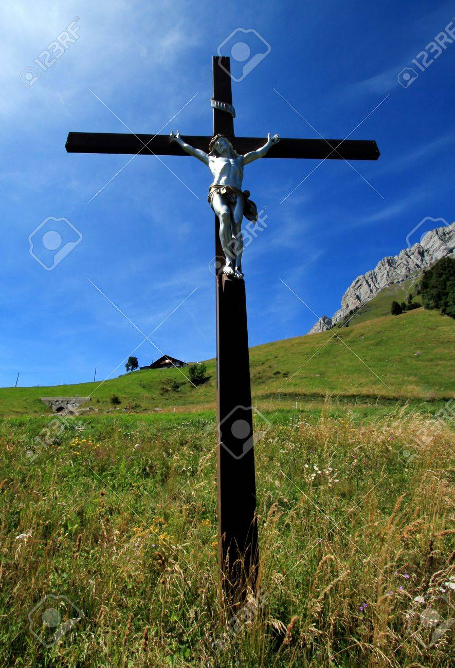 white sculpture of jesus on a wood cross in the green mountain