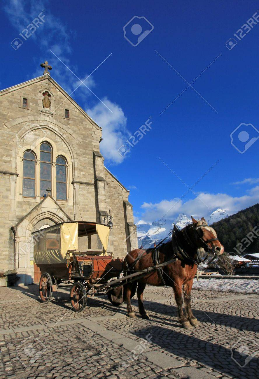 Brown horse and carriage in front of Notre-Dame de l'Assomption church by beautiful day, Grand-Bornand, France Stock Photo - 17431424