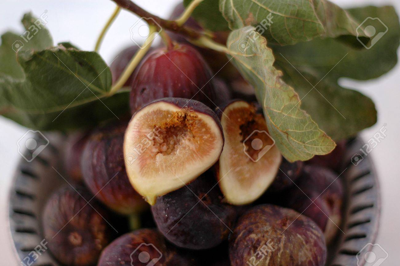 Whole and cut Figs in an hand thrown ceramic bowl with fig leaves. Extreme shallow depth of focus. Stock Photo - 300392
