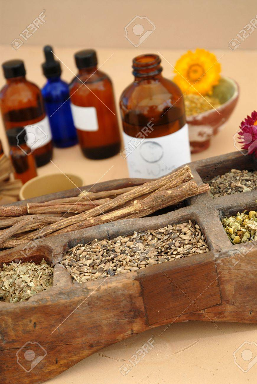 The holistic ingredients of Ayurveda and Herbalism including licorice root, milk thistle seeds, valerian root, chamomile, and tincture bottles. - 916843