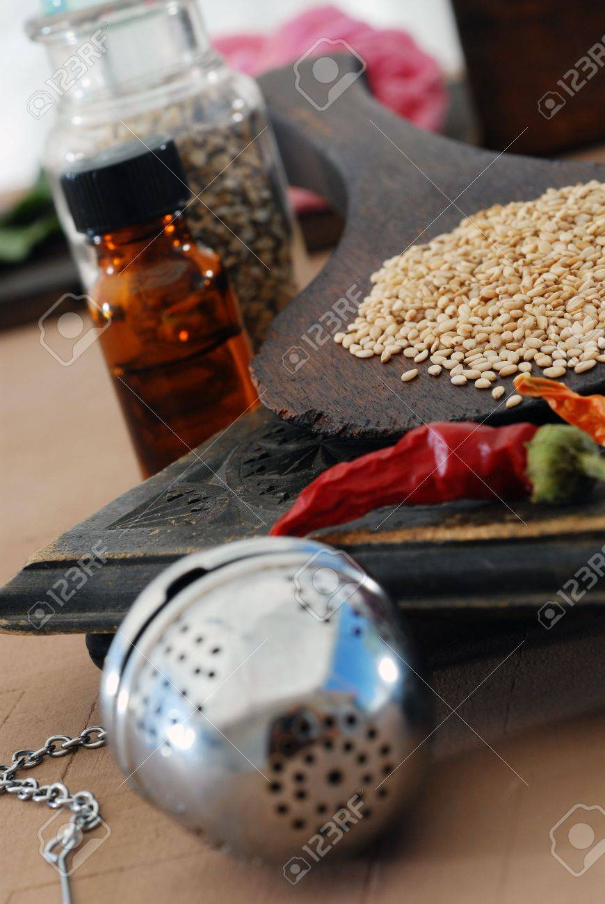 Some of the basic elements of Ayurveda: sesame, chili, tincture, tea ball, and herbs. - 2113603