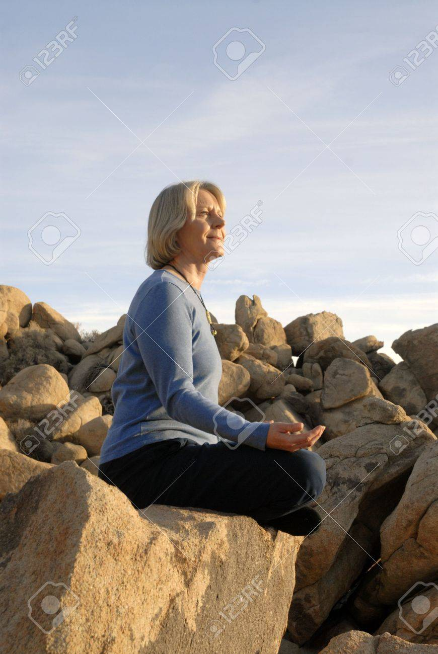 Woman in yoga meditiation pose outdoors in the boulders. - 2586518