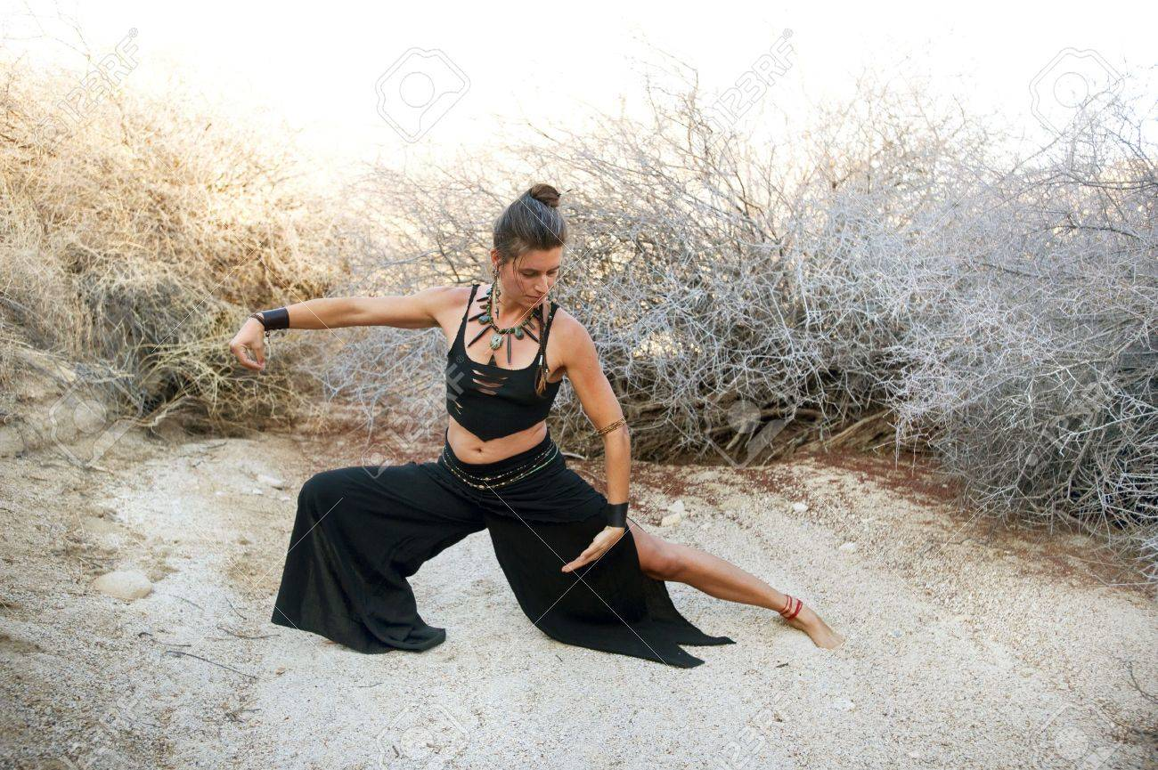 Woman with beautiful style practicing Tai chi in a natural desert environment. Art Medicine Adornment. - 6862790