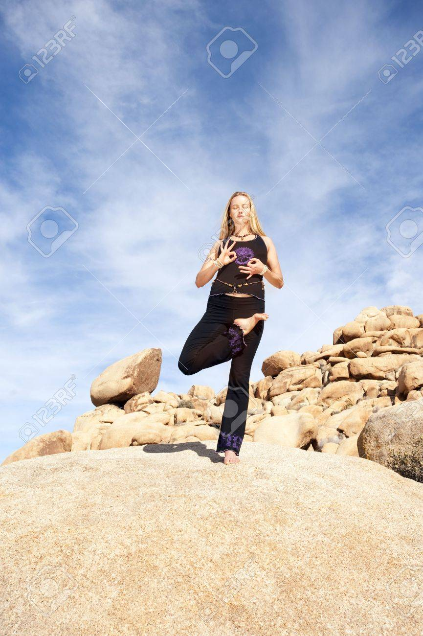 Wide shot of a young beautiful woman in yoga tree pose on a huge boulder with a big sky. Elise Kost Jewelry. Stock Photo - 6862785