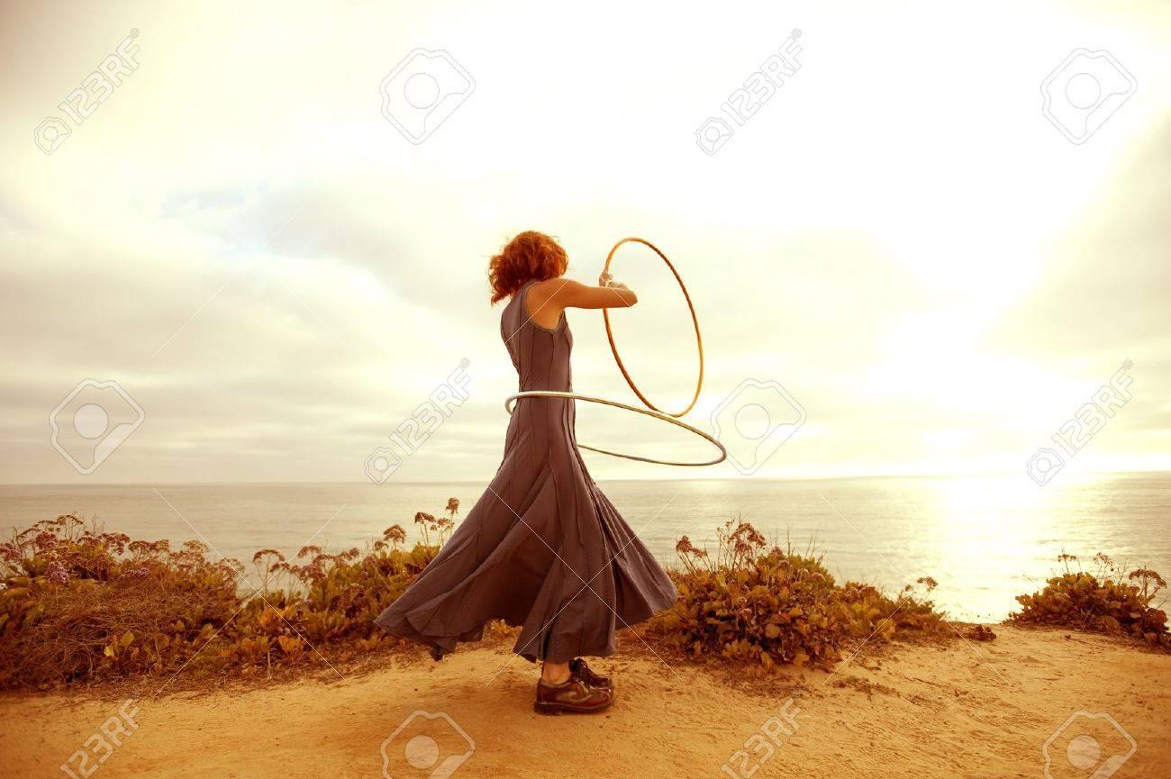 A woman hooping in the sunset. - 7351813