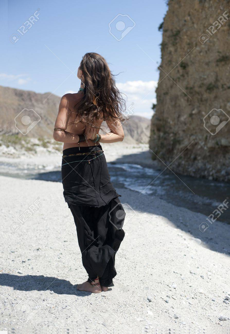 Beautiful young woman seen from the back standing near a desert river with her hands in a reverse yoga mudra. Stock Photo - 8216486