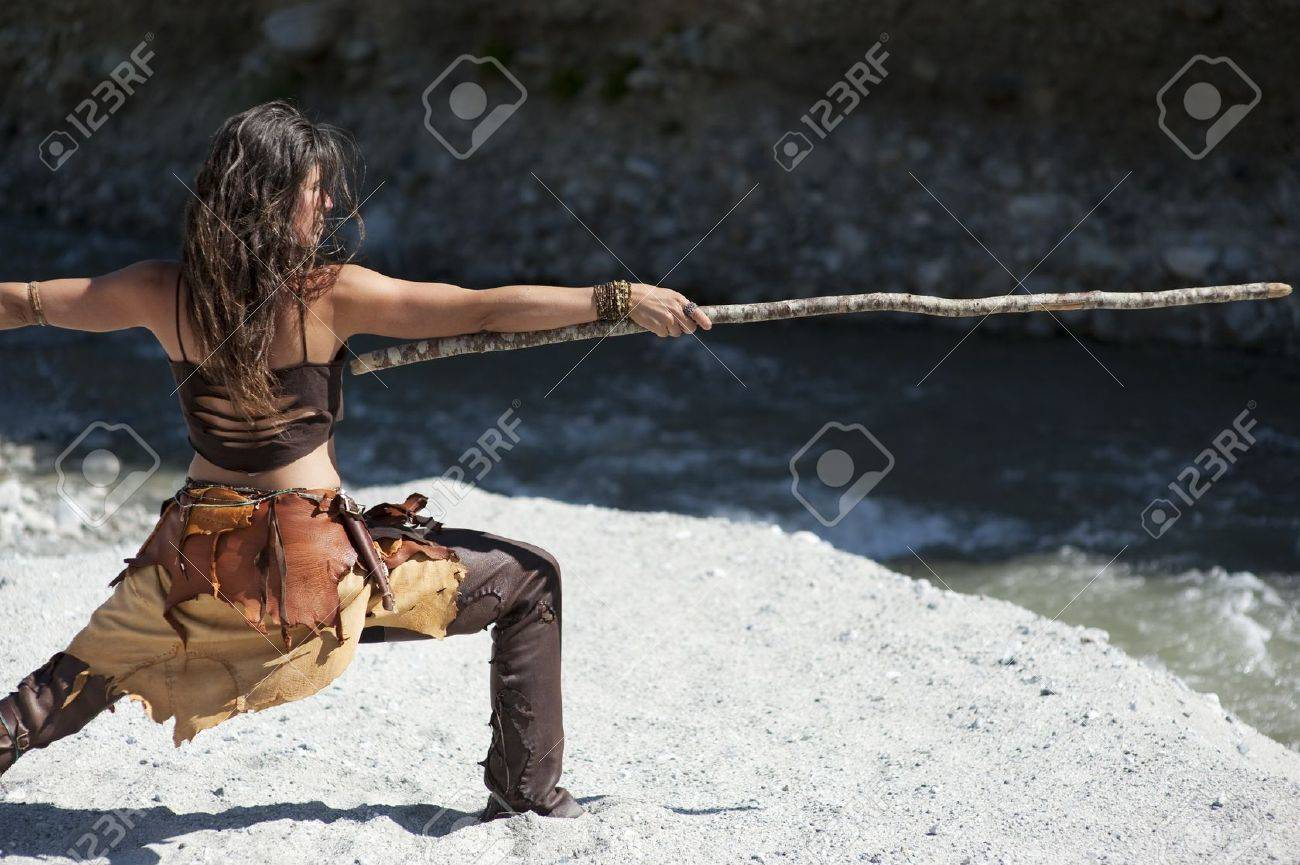 Woman in tribal style practicing self defense with a longstick. - 8216468