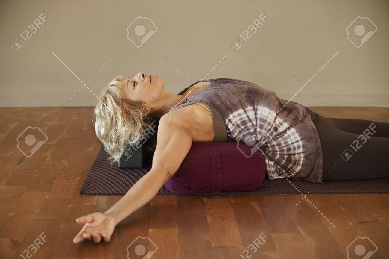 Middle age woman resting on a yoga bolster. - 9189848