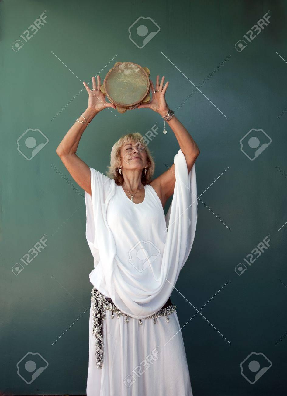 Woman in white raising a tamborine over her head. - 9189851