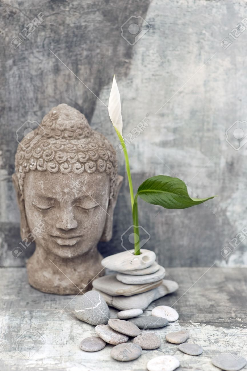 Stone Buddha head sculpture photographed with a white flower and stones - 15512579