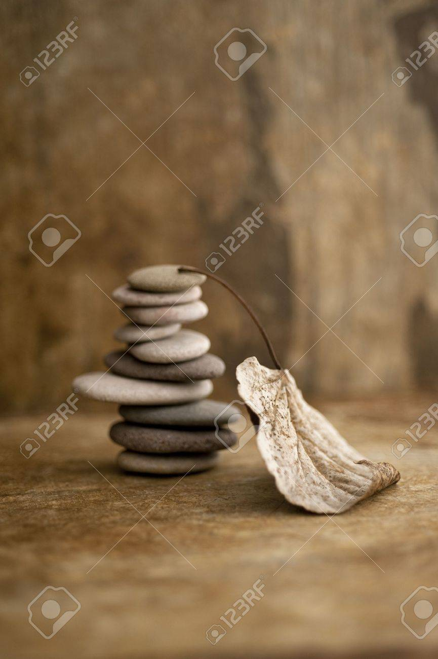 Stacked stones and a fallen leaf in a earth toned setting - 15512580