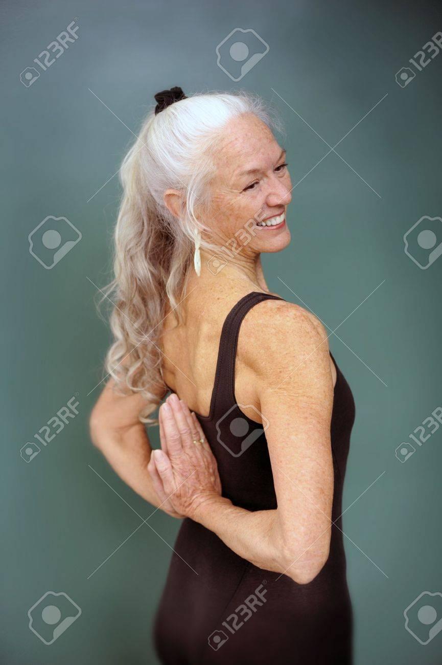 Senior woman in the yoga pose reverse prayer. - 15302389