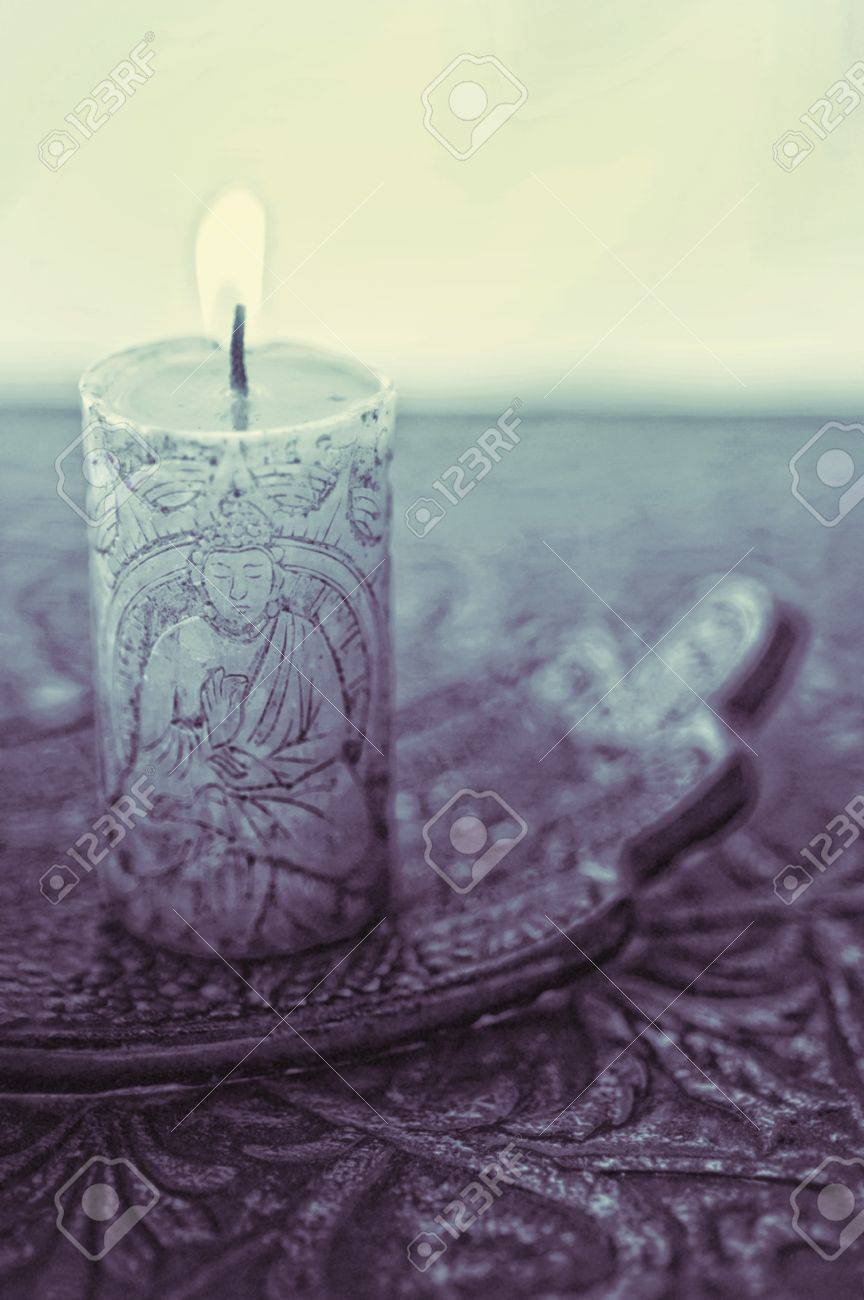 A lit buddha candle in a simple setting - 17134858