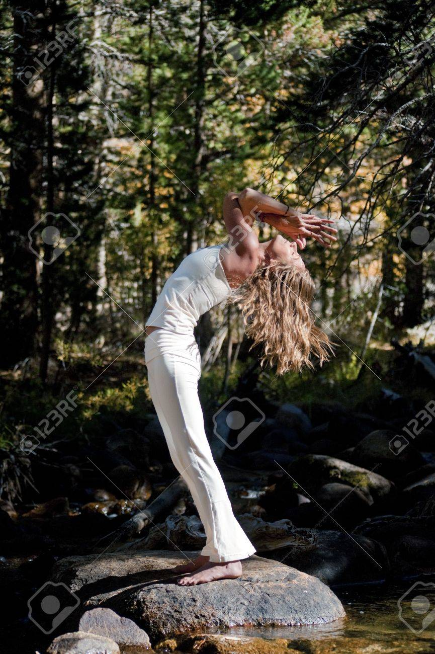 Semi silhouette of Woman in yoga pose outdoors in the wods - 17162532