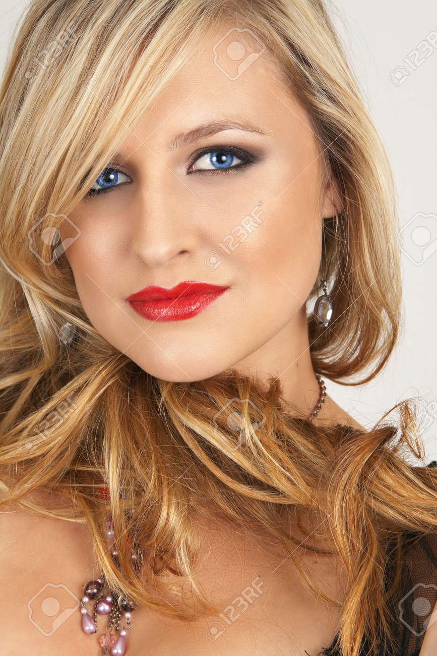 Portrait of a beautiful blonde woman with light blue eyes and evening make-up on