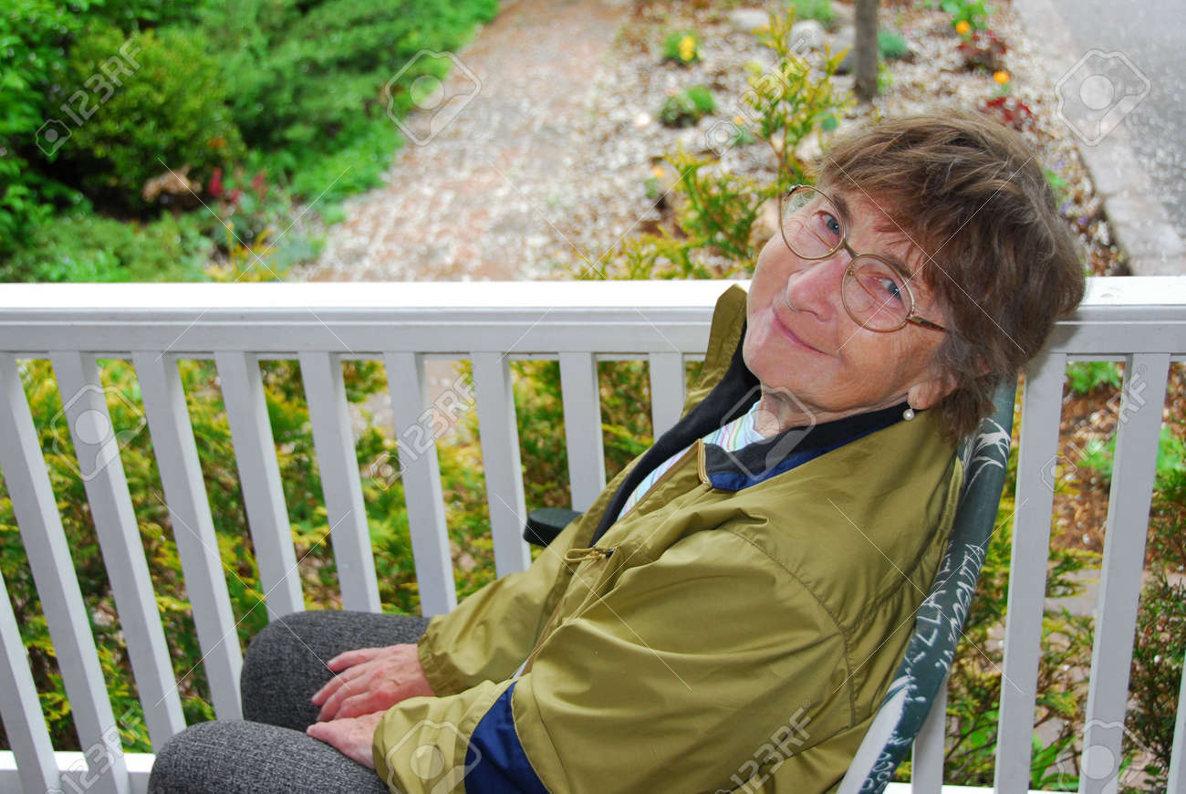 Senior woman sitting on a porch and smiling Stock Photo - 408420