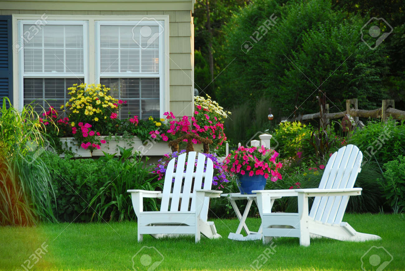 Stock Photo   Two Lawn Chairs In A Beautifl Garden
