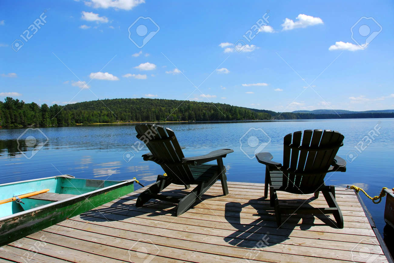 Stock Photo   Two Adirondack Wooden Chairs On Dock Facing A Blue Lake With  Clouds Reflections