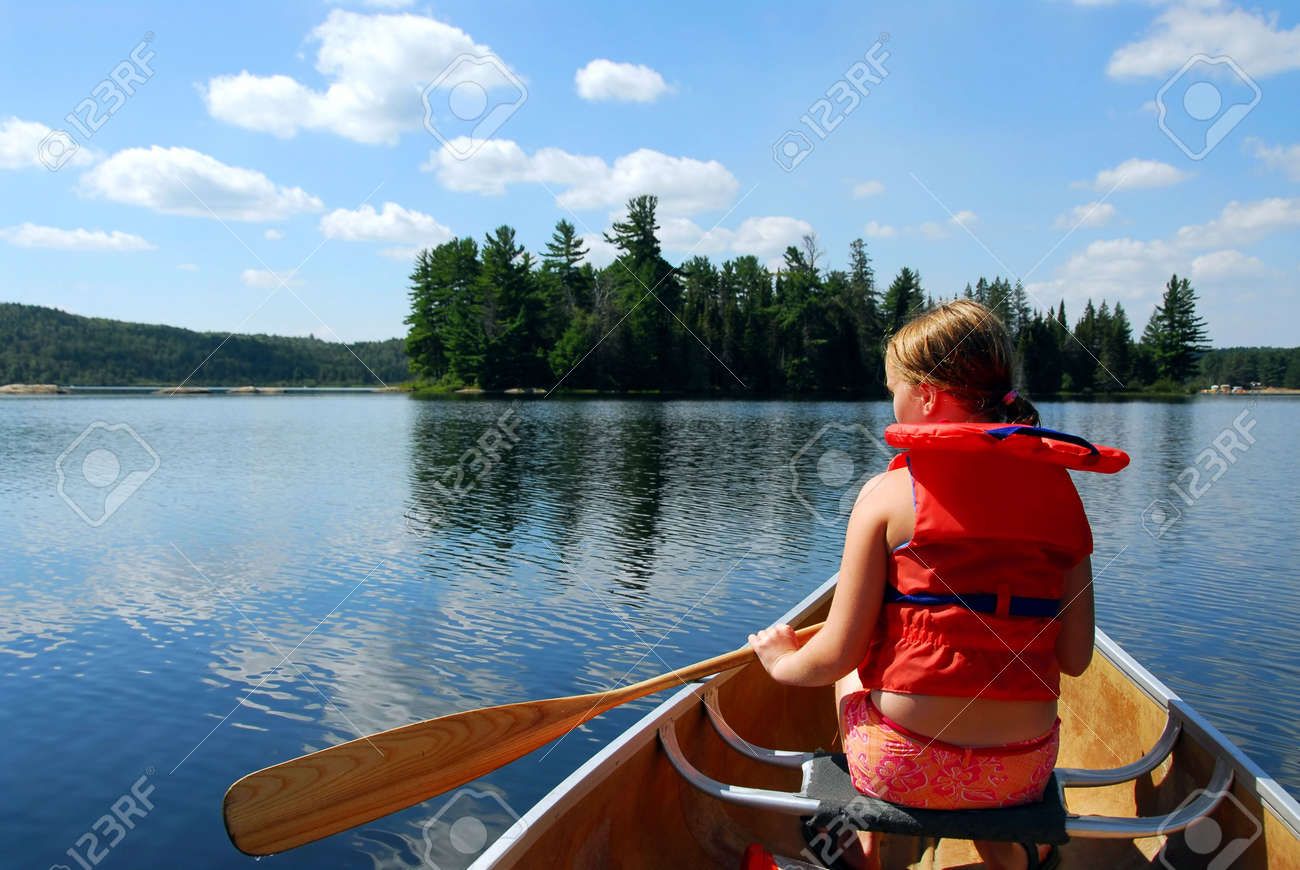 Young girl in canoe paddling on a scenic lake Stock Photo - 546819