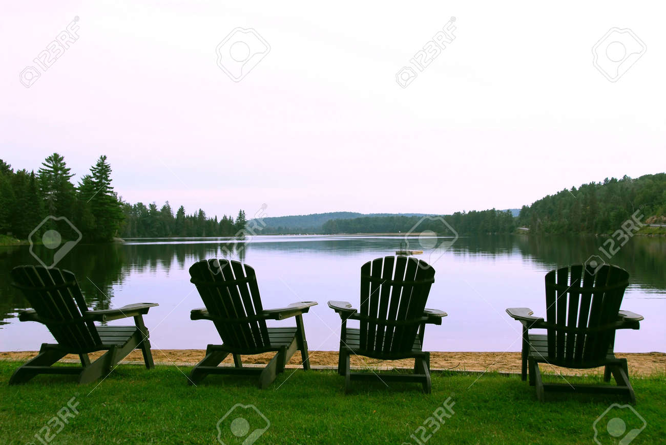 Four Wooden Adirondack Chairs On A Shore Of A Beautiful Lake At Dusk Stock  Photo