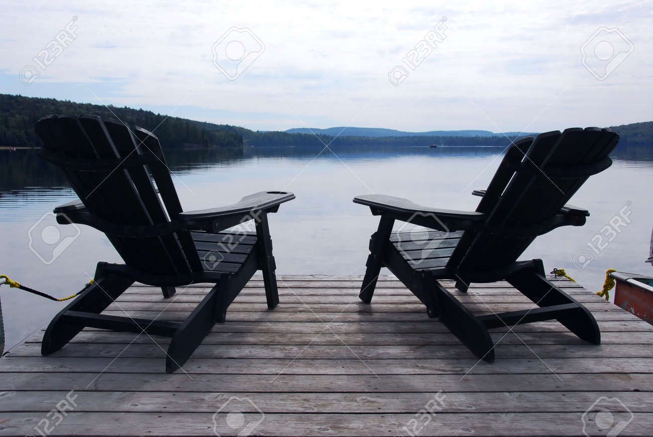 Stock Photo   Two Wooden Adirondack Chairs On A Boat Dock On A Beautiful  Lake In The Evening