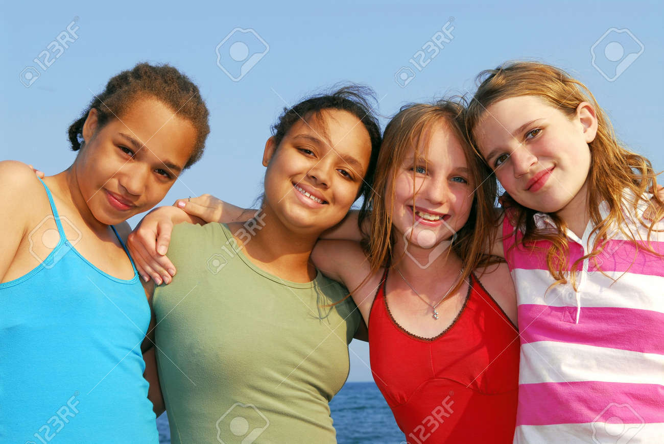 pre teens preteens happy diverse: Portrait of four smiling teenage girls outside  Stock Photo