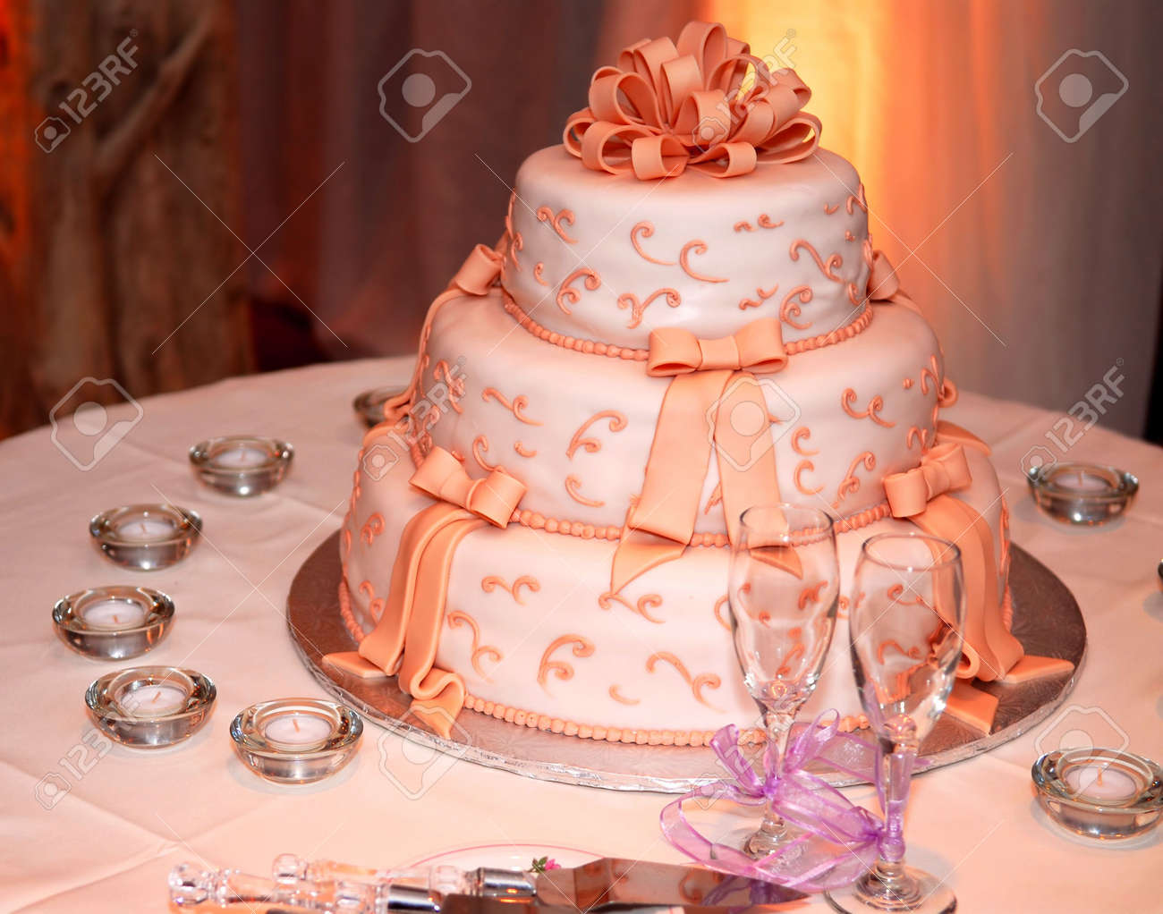 Three Tiered Wedding Cake And Champagne Glasses On A Table Stock ...