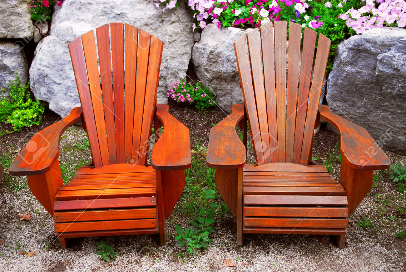 Two Solid Wood Patio Chairs And Natural Stone Landscaping Stock