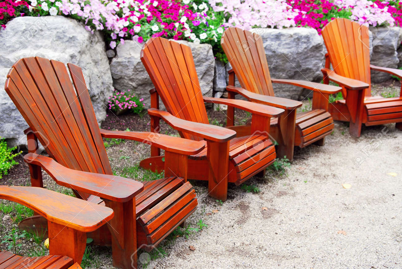 Row Of Solid Wood Patio Chairs And Natural Stone Landscaping Stock Photo    1576771