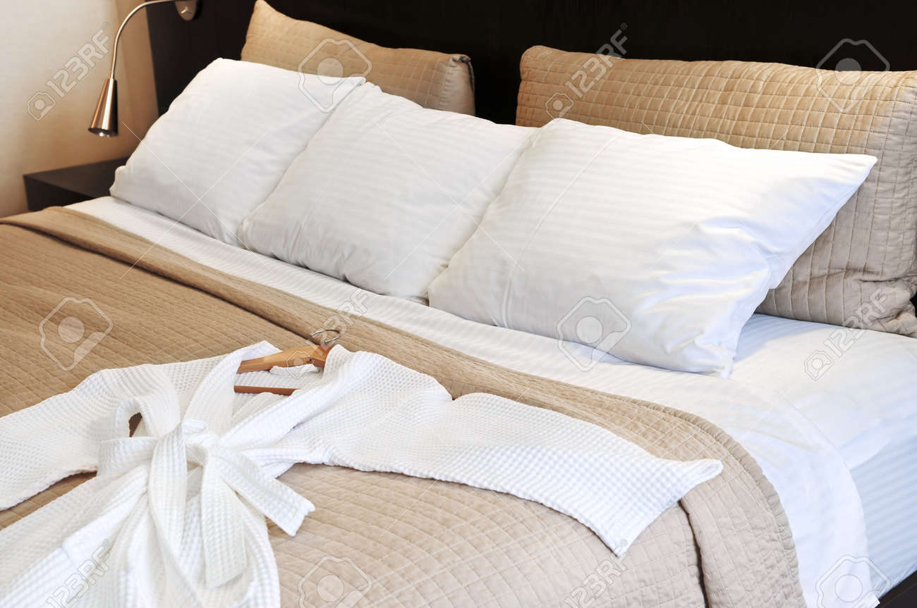 Comfortable bed with clean bathrobe in upscale hotel Stock Photo - 3102167