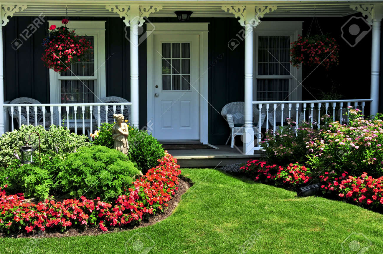 landscaped front yard of a house with flowers and green lawn stock