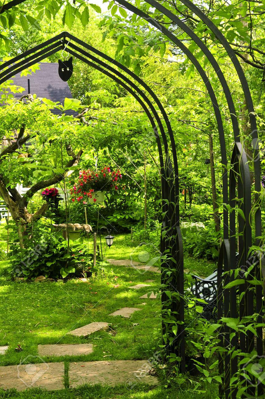 Lush vert jardin avec tonnelle en fer forgé