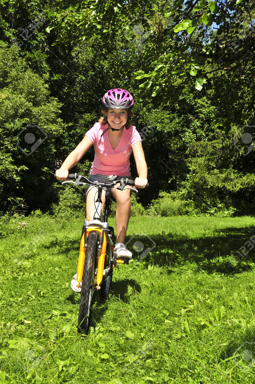 Portrait of a teenage girl riding a bicycle in summer park outdoors Stock Photo - 3930827