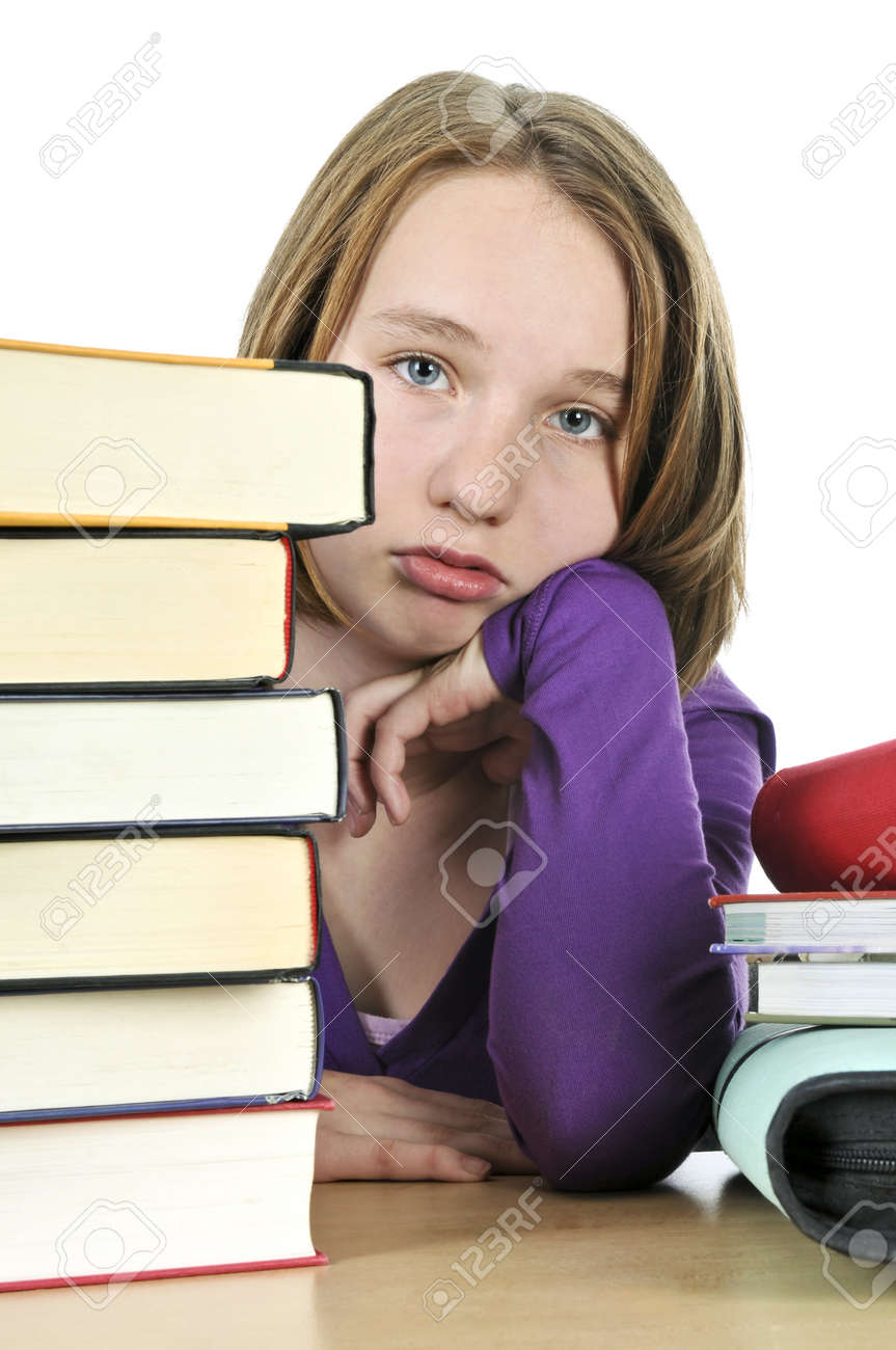 Frustrated teenage girl studying at the desk with big stack of books - 4015636