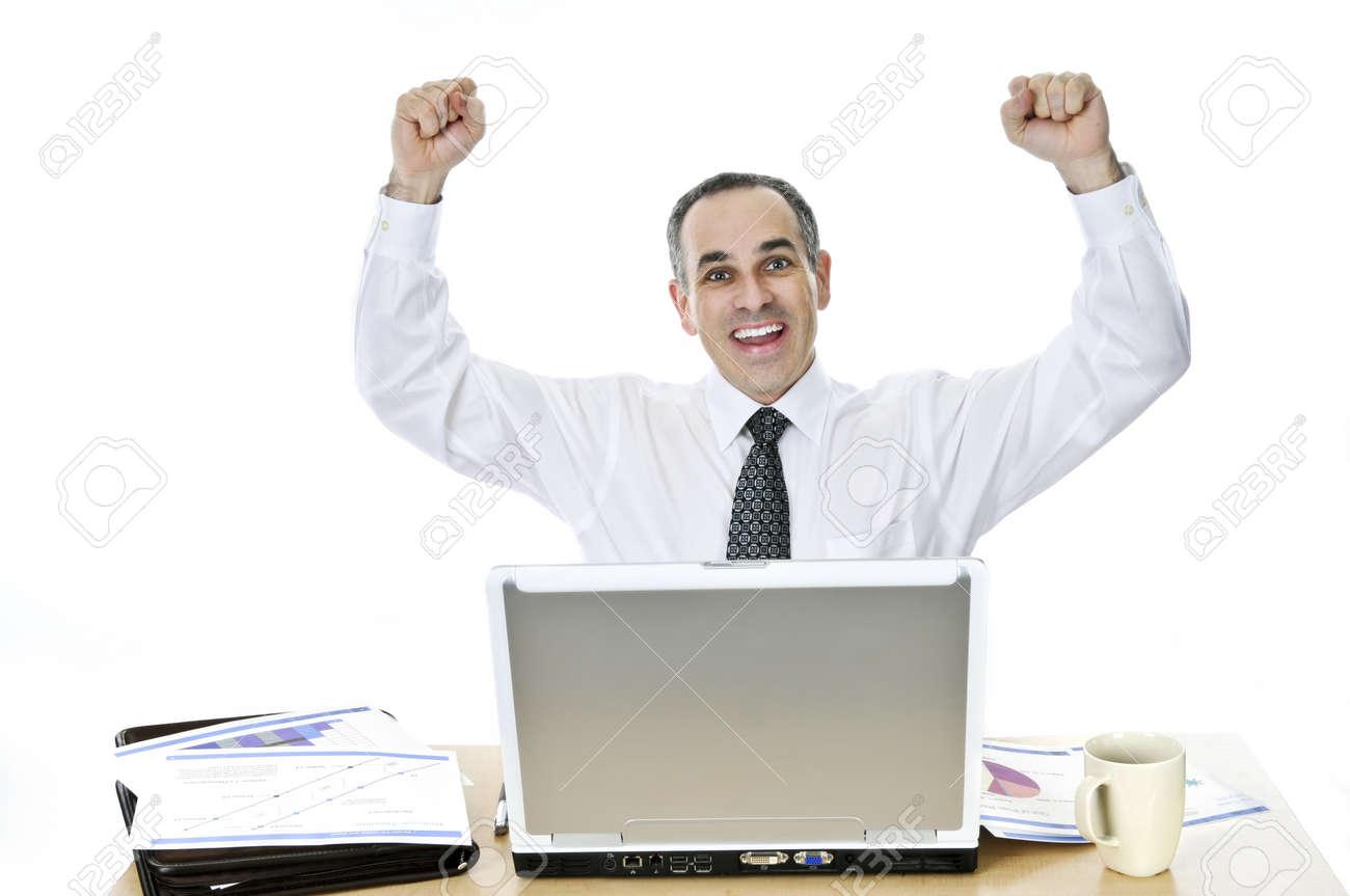 Happy businessman levant son bras assis à son bureau isolé sur