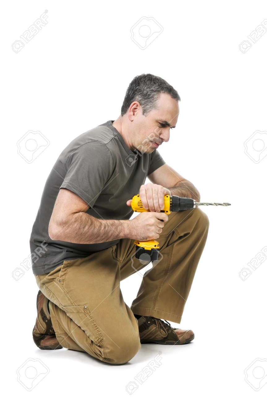 Kneeling handyman pushing on his cordless drill Stock Photo - 4160308