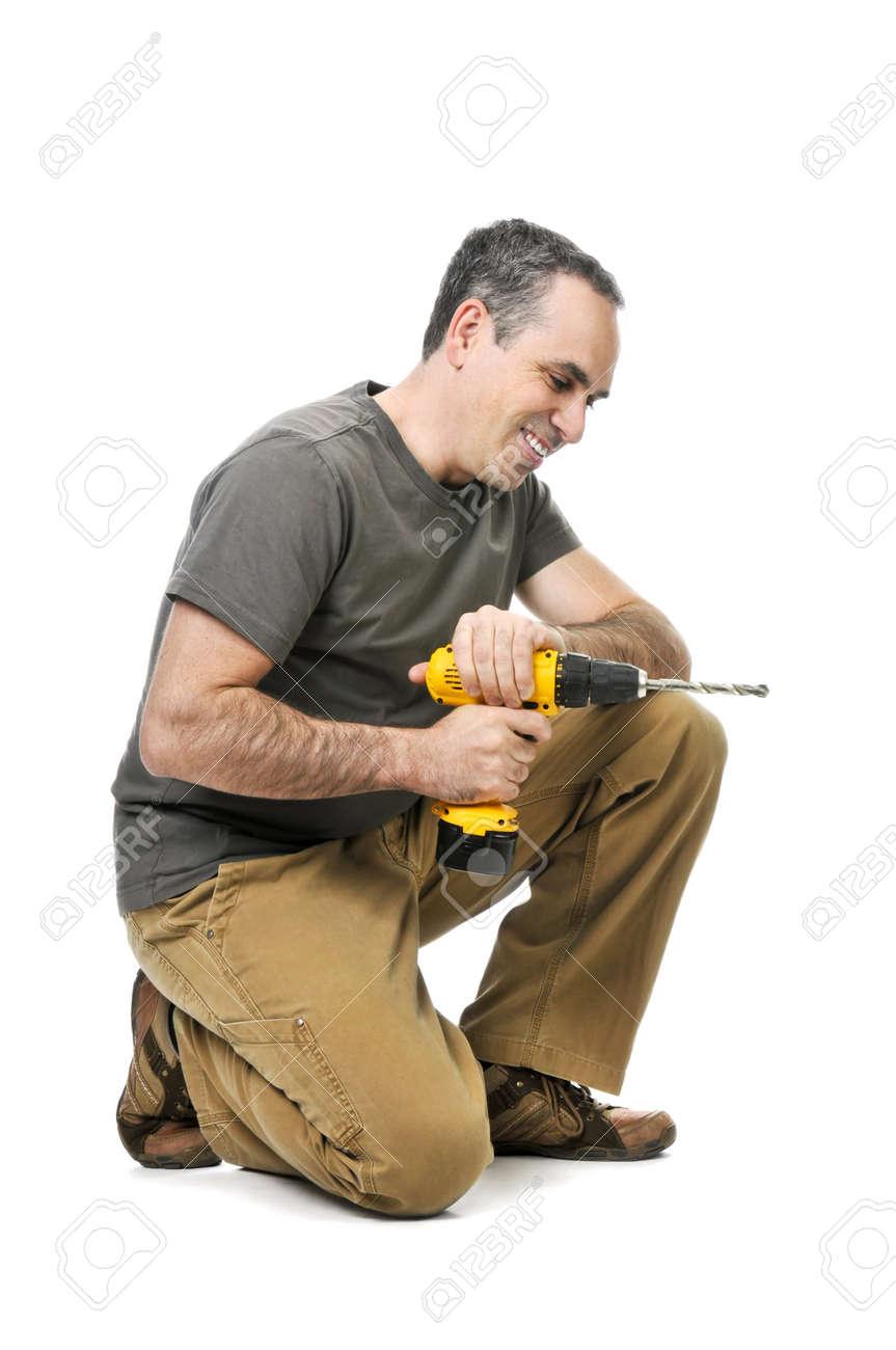 Kneeling handyman pushing on his cordless drill Stock Photo - 4184545