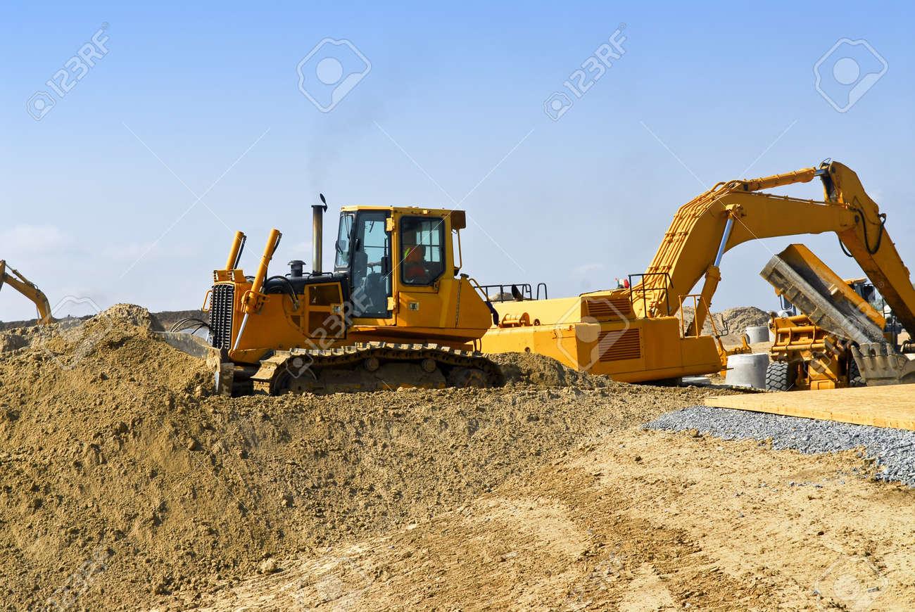 yellow bulldozer machines digging and moving earth at construction
