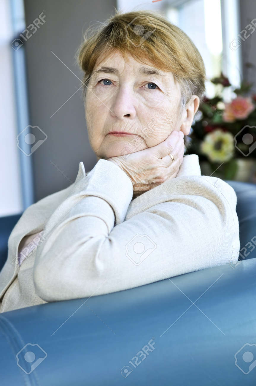Sad elderly woman sitting on a couch indoors Stock Photo - 4440489