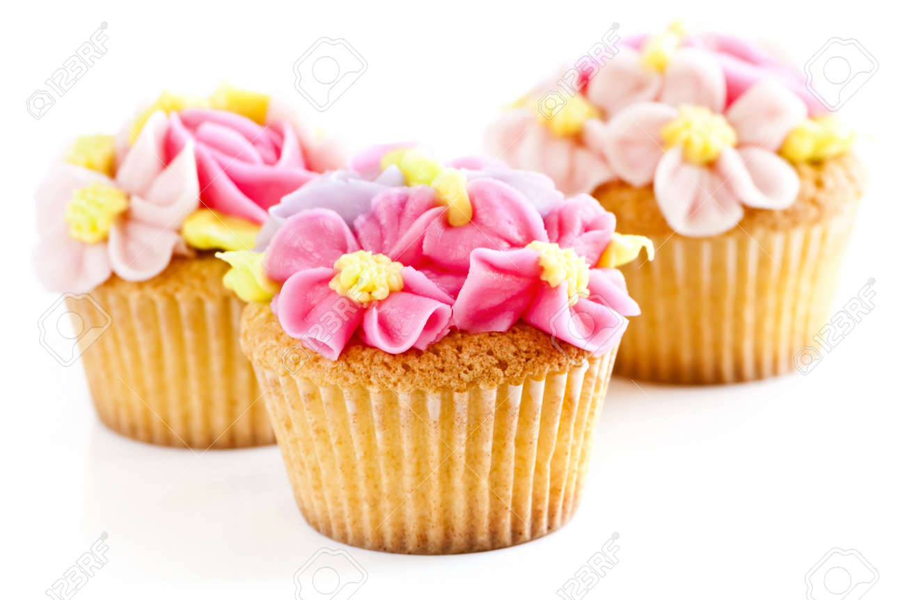 Three Tasty Cupcakes With Icing Flowers On White Background Stock