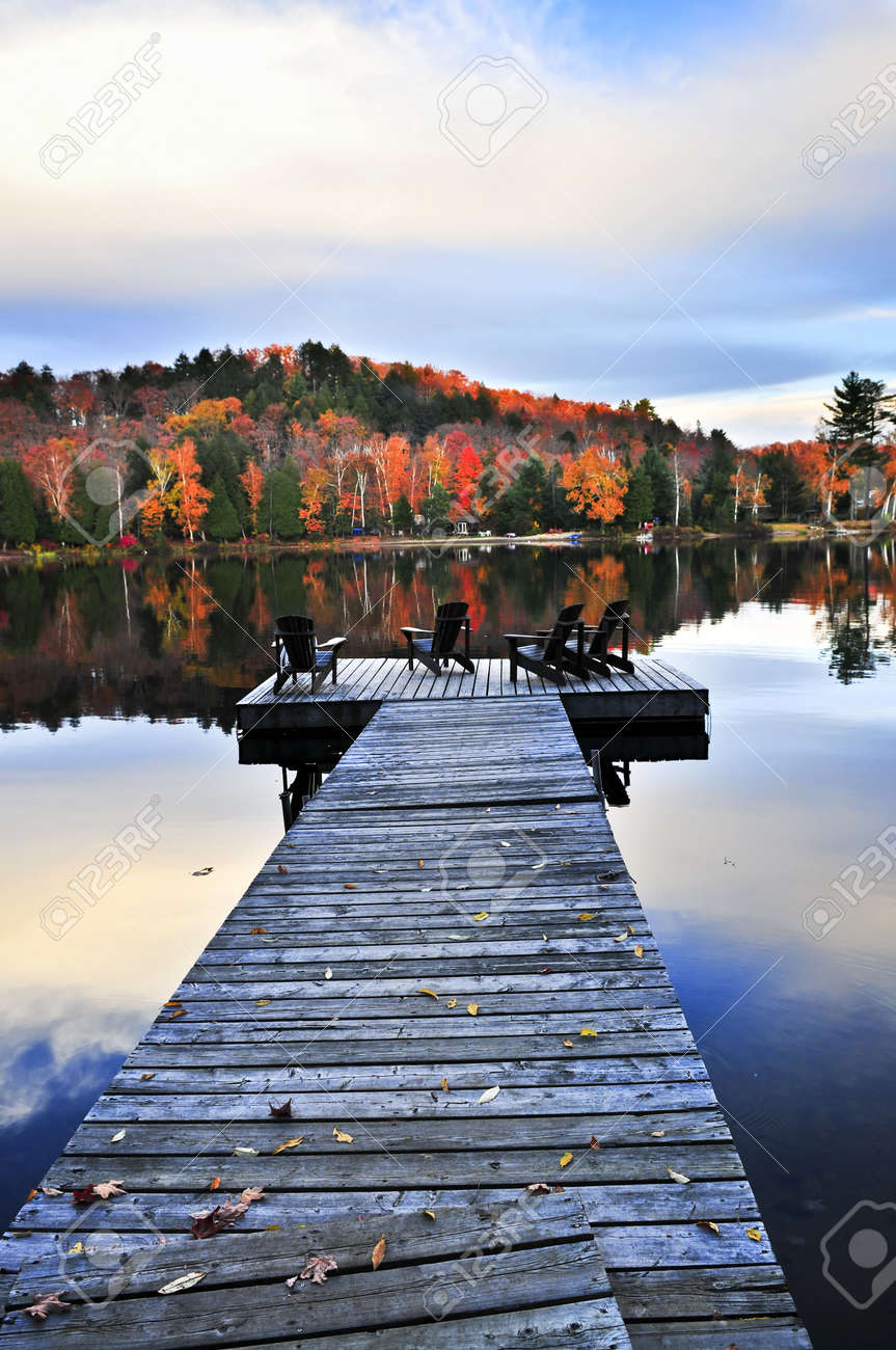Stock Photo   Wooden Dock With Chairs On Calm Fall Lake