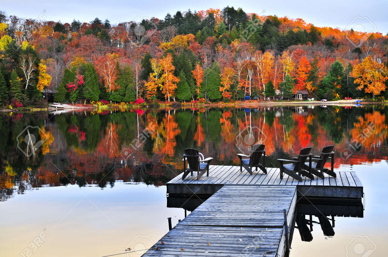 Wooden dock with chairs on calm fall lake Stock Photo - 5139556