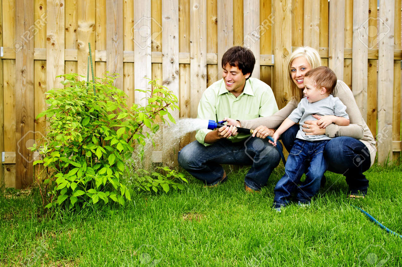 happy family in backyard watering plant with hose stock photo