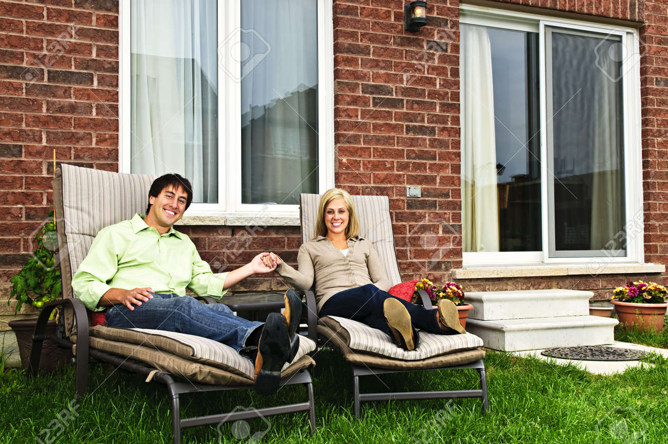 Magnificent Happy Couple In Backyard Of New Home Sitting On Lounge Chairs Beatyapartments Chair Design Images Beatyapartmentscom
